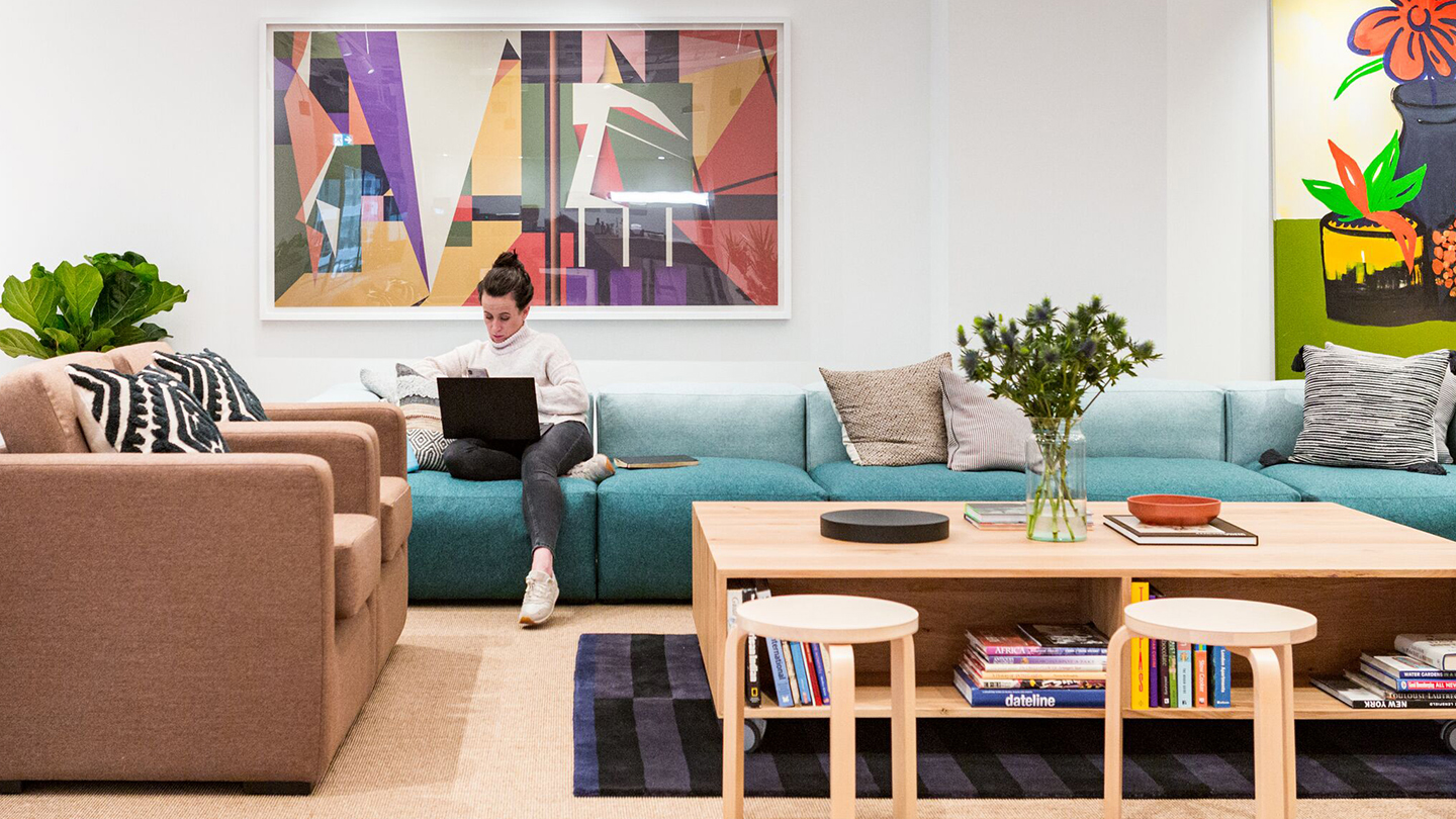 "img src=""wework30churchill.jpg"" alt=""woman working on laptop sitting on couch in coworking space"">"