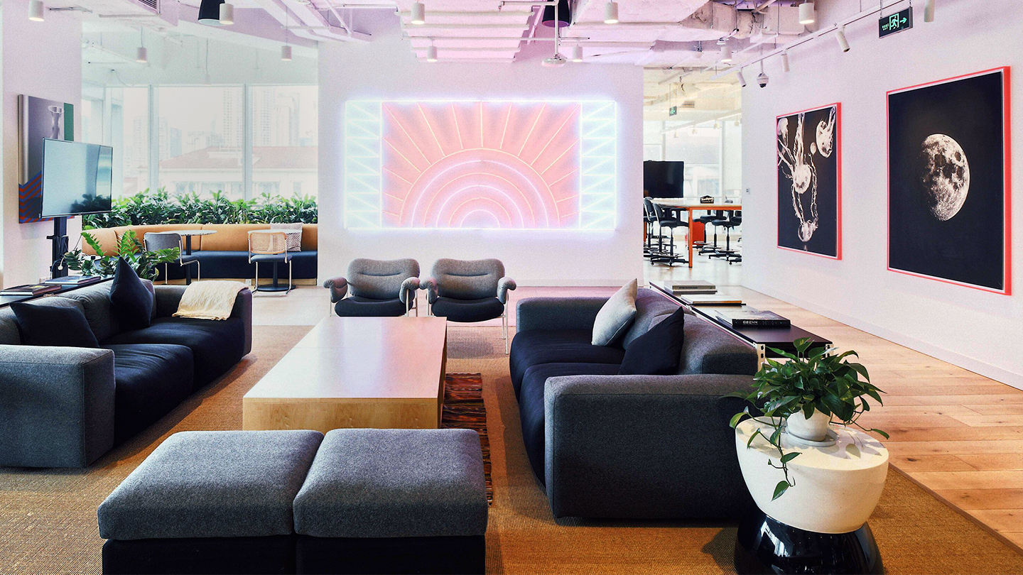 "img src=""weworkchinaoverseasinternationalcenterl.jpg"" alt=""open floor plan coworking area with neon art work in China"">"